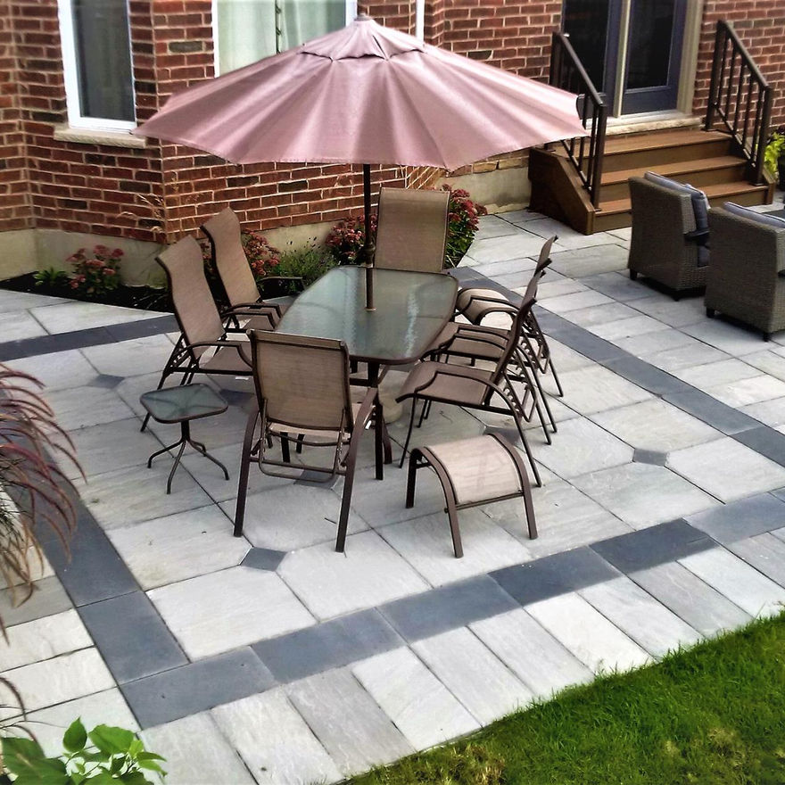 Banas dove gray square cut flag stone with coda black border and inlays. Custom patio installation in London, Ontario.